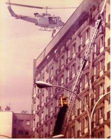 Capt. Rees at controls with TSgt. Pighini on hoist above burning hotel